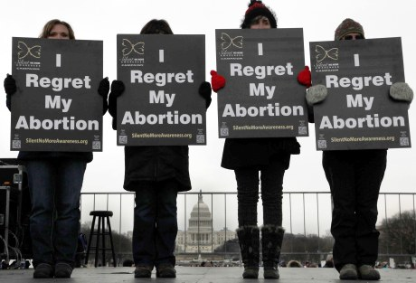 Activists hold signs during annual March for Life rally in Washington